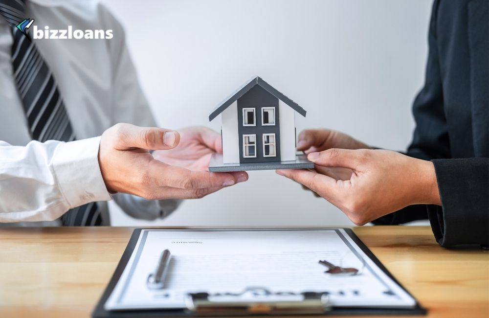 Two hands of business owners holding a Miniature of House