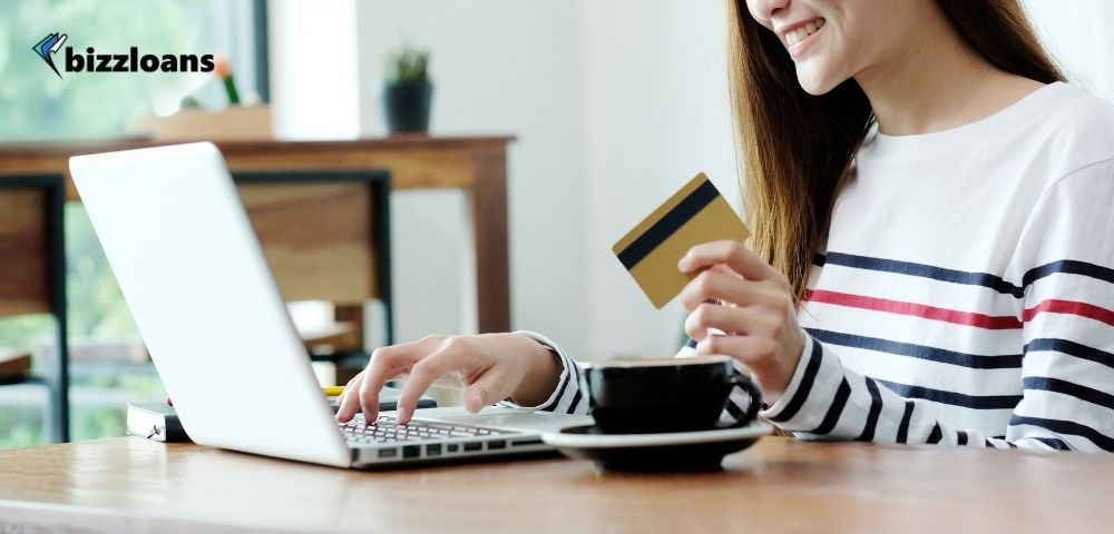 Young asian woman holding a business credit card while using her laptop at home