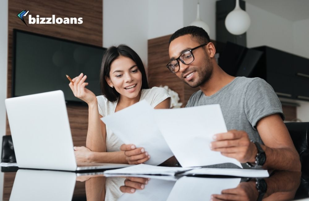 happy business owners analyzing the need for cash flow loan using laptop