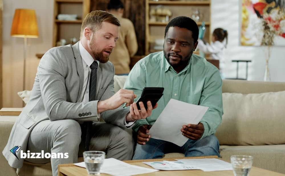 Business owner with professional adviser sitting on couch with calculating machine discussing small business loan interest rates