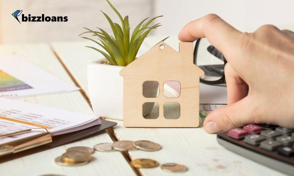 man's hand touching a miniature of a house as a collateral to his small business loan