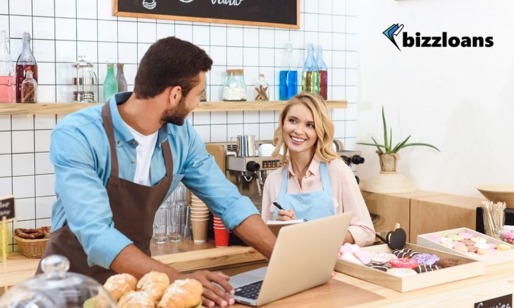 two cafe owners using a laptop in the counter while smiling at each other