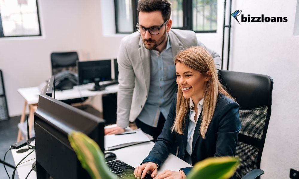 Male business owner delegating work to a female staff while working on a computer