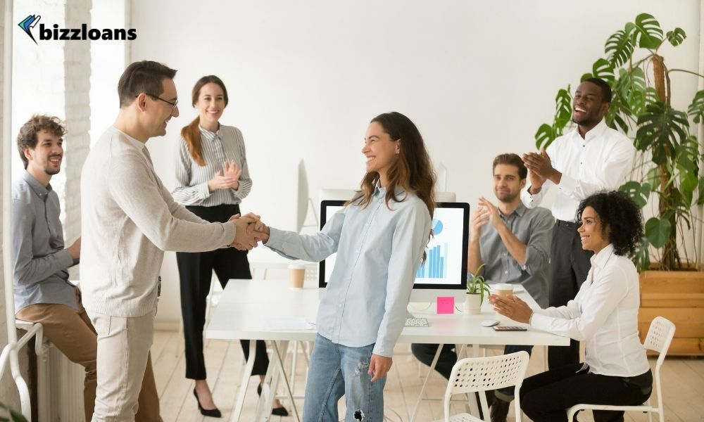 Manager congratulating a female staff in front of other employees in the office