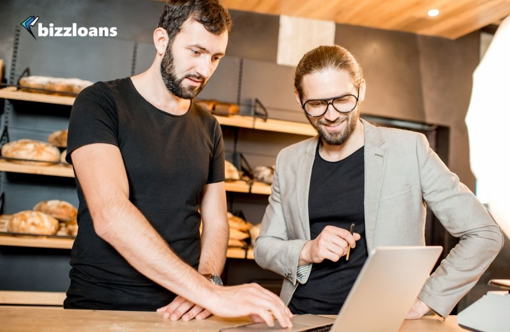two business owners looking at a laptop using ai for their small business