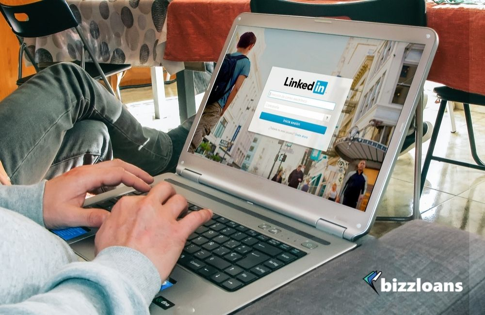 hands of a business owner using a laptop displaying LinkedIn login page