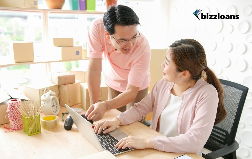 two business owners smiling at each other while checking on how to improve financial position in the laptop