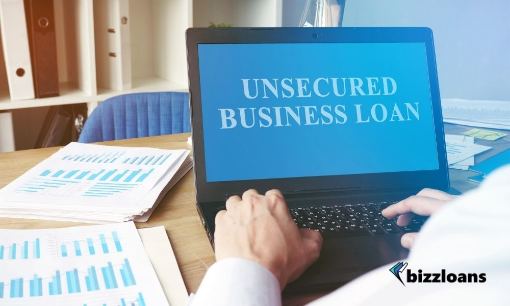 hands of a business owner using a laptop displaying unsecured business loan