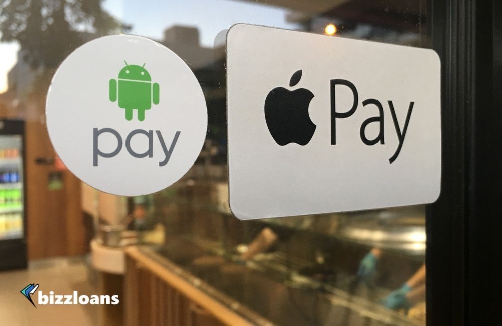 Apple and Android Pay stickers on a door to a restaurant which are two of the best mobile payment apps