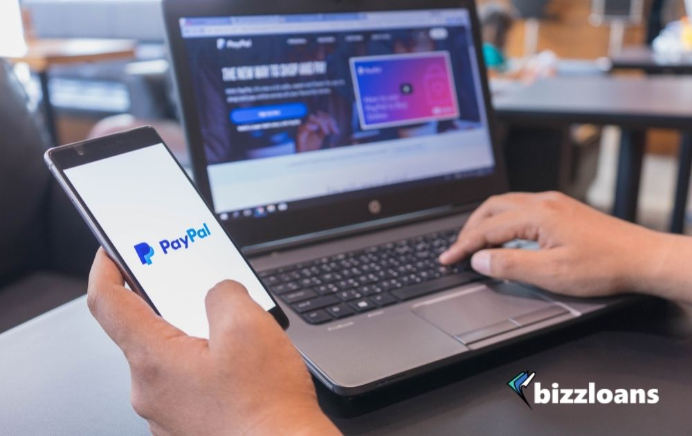 Hand of a businessman paying with smartphone and laptop displaying PayPal logo on screen