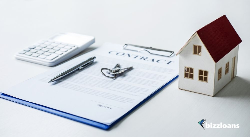 House model, calculator and house key lying on real property contract for business expansion