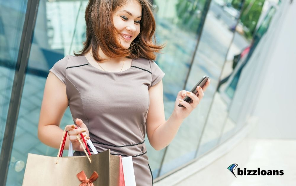 Happy fashion woman with shopping bags using mobile phone, shopping center
