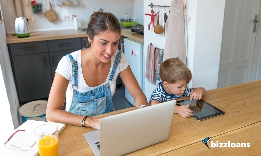 small business owner working from home on her laptop with her kid on the side
