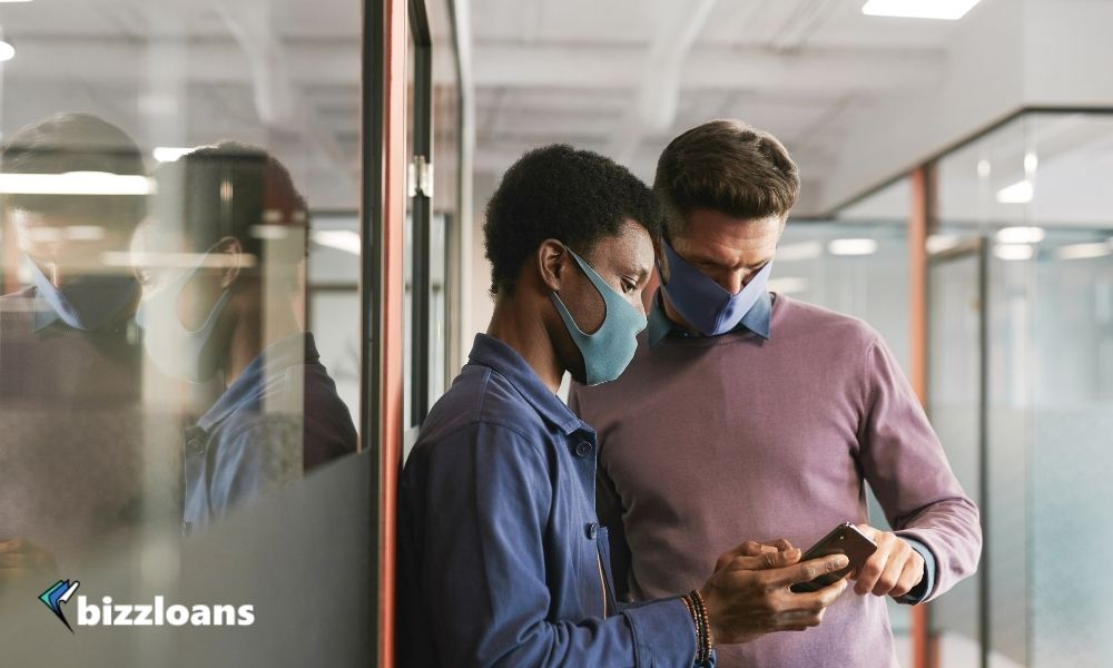 two small business owners looking at a smartphone wearing masks in the office